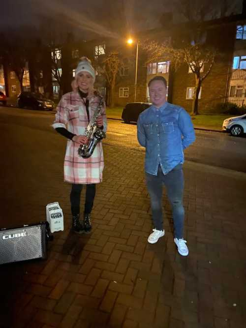 Kay with saxophone stood next to a customer on a driveway