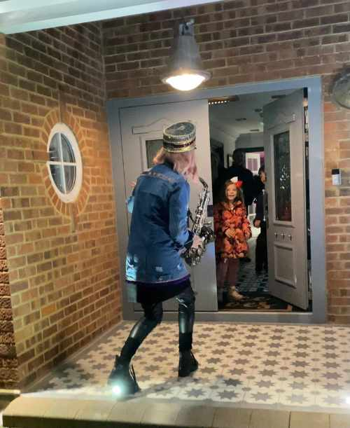 Kay with saxophone surprising young customer at her front door
