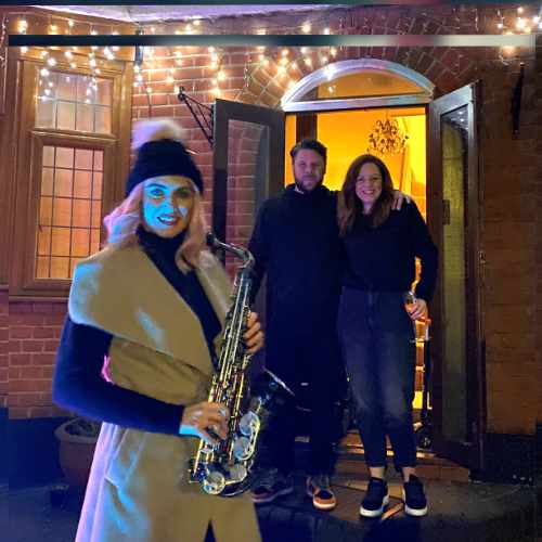 Doorstep sax. Photo of Kay performing to a couple at their doorstep