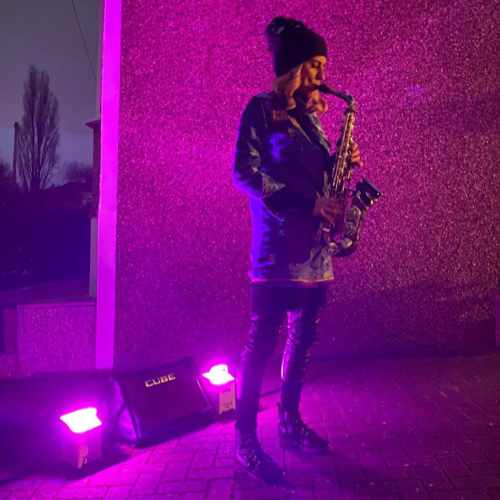 Doorstep sax. Photo of Kay performing on a pink floodlit driveway