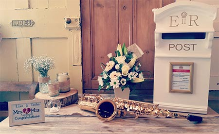 Wedding photo with happy couple plaque flowers, sax and e.r. post box